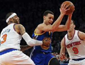 Golden State Warriors' Curry drives between New York Knicks' Martin and Prigioni in their NBA basketball game in New York